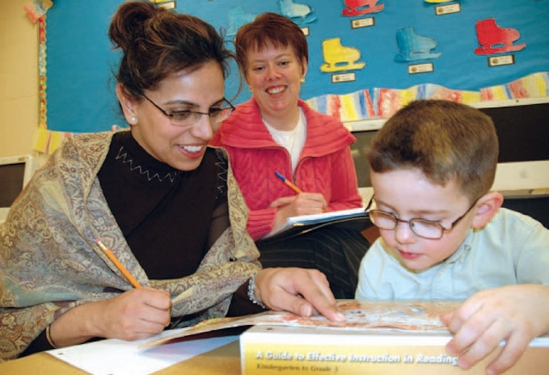 Teachers helping young student read