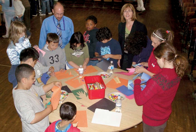 students standing at round table creating art from construction paper