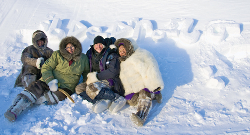 aboriginal women wearing parkas sitting in the snow