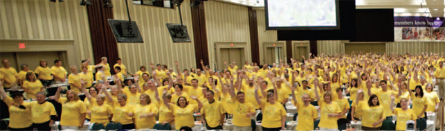 crowd of ETFO members wearing yellow shirts with hands in the air