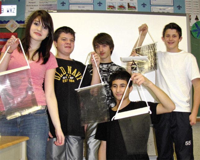 students posing with their art projects