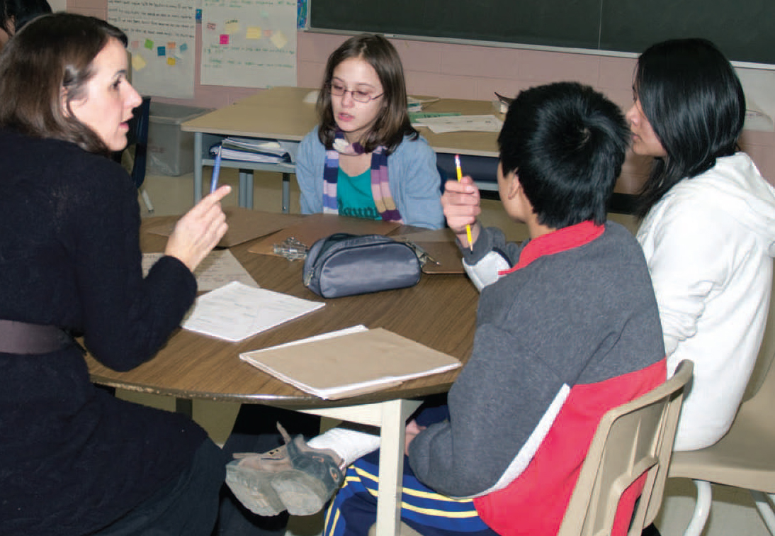 teacher sitting with three elementary students at a desk in classroom
