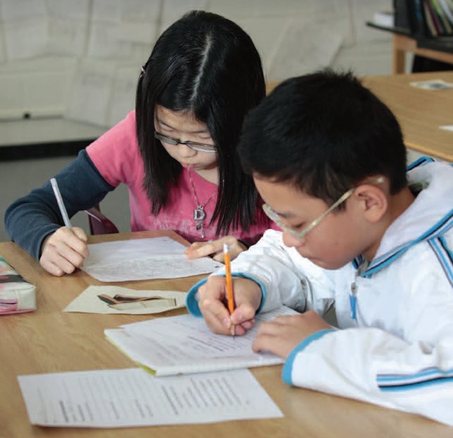 two students writing on paper with pencils in classroom