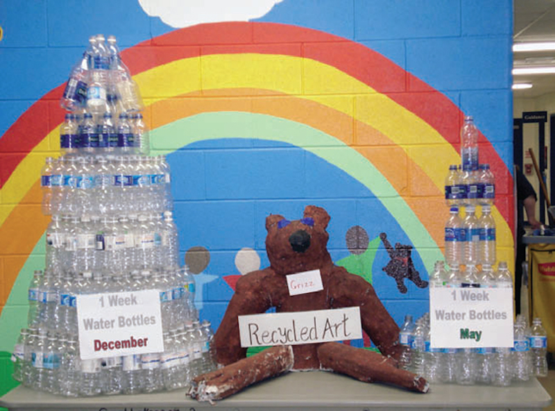 student project of towers constructed from water bottles with a rainbow painted on brick wall in background