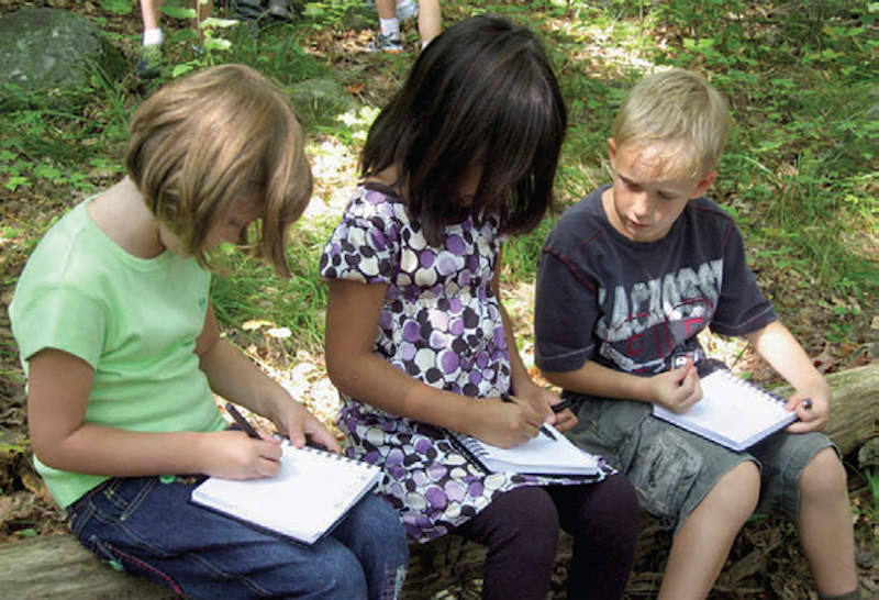 three young elementary students sitting on stone outside writing in notebooks