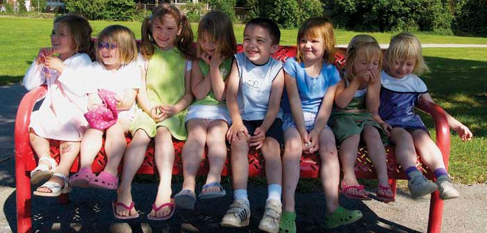 8 kindergarten students sitting on bench