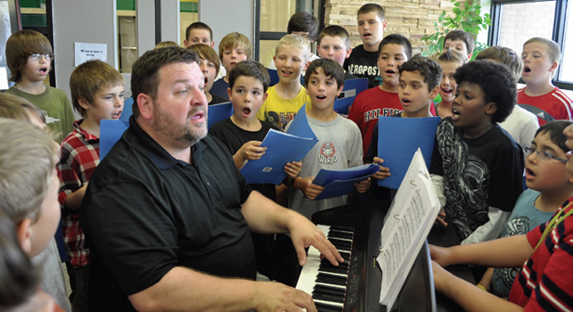 music teacher singing and playing keyboard surrounded by students who are also singing