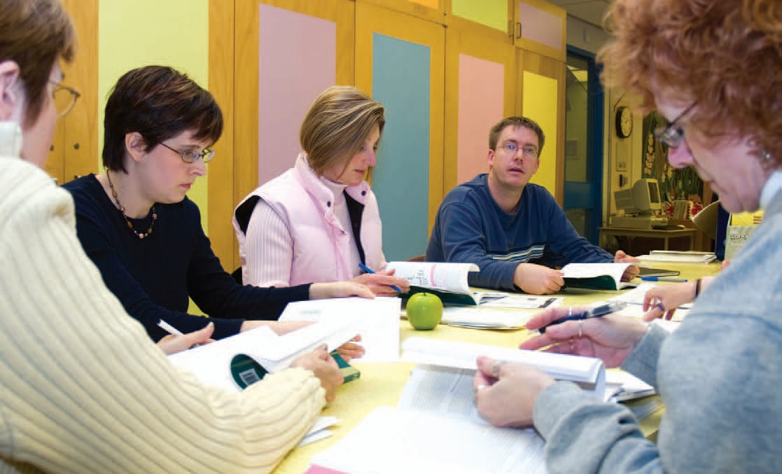etfo members sitting around table discussing content in textbooks