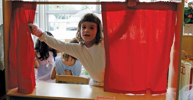 young girl opening red curtain