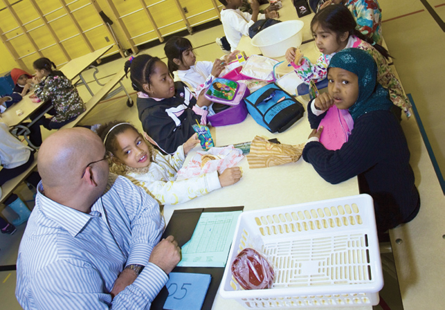 teacher sitting with students at large table in cafeteria