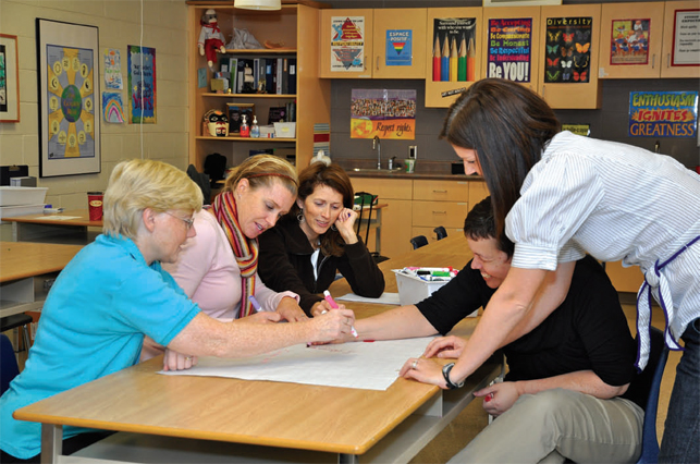 group of teachers writing on large white paper in a classroom