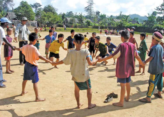 Young children holding hands in circle while two children chase one another within