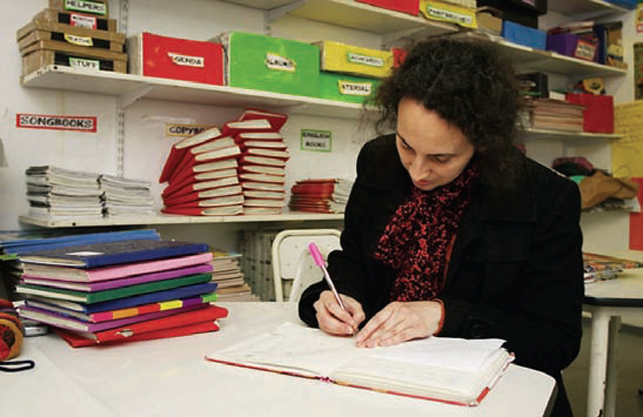 teacher sitting in office writing in book