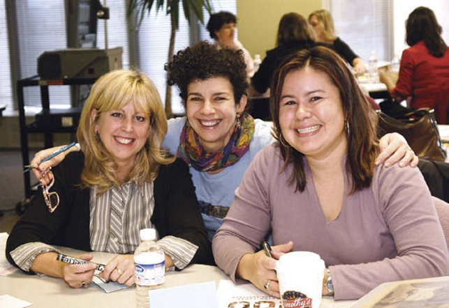 three women sitting together posing with smiles for camera