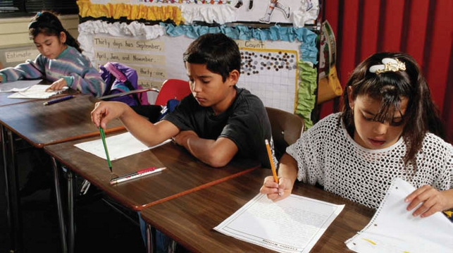 three students sitting at desks writing on paper