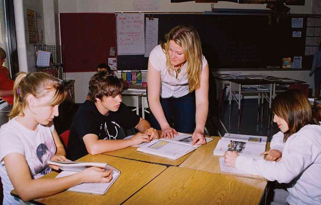 teacher leaning over desk speaking with students that are reading textbooks
