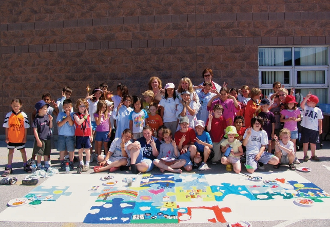 elementary class standing outside of school with artwork in front of them