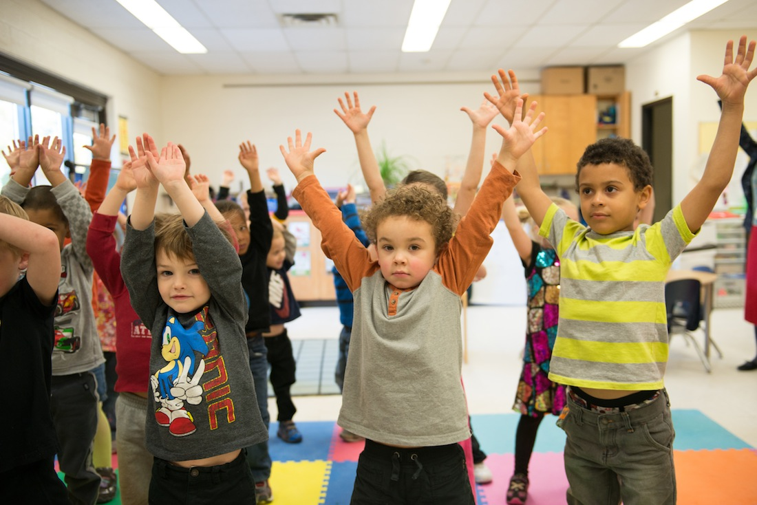 Young elementary students stretching in classroom
