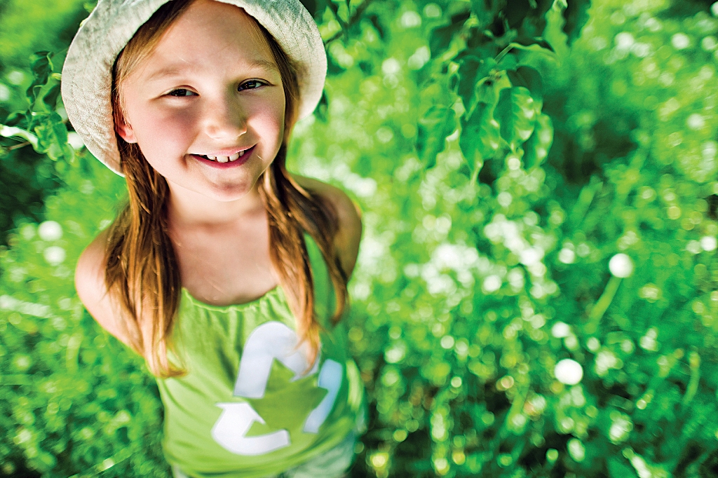 Young girl wearing green recycle shirt in field of grass