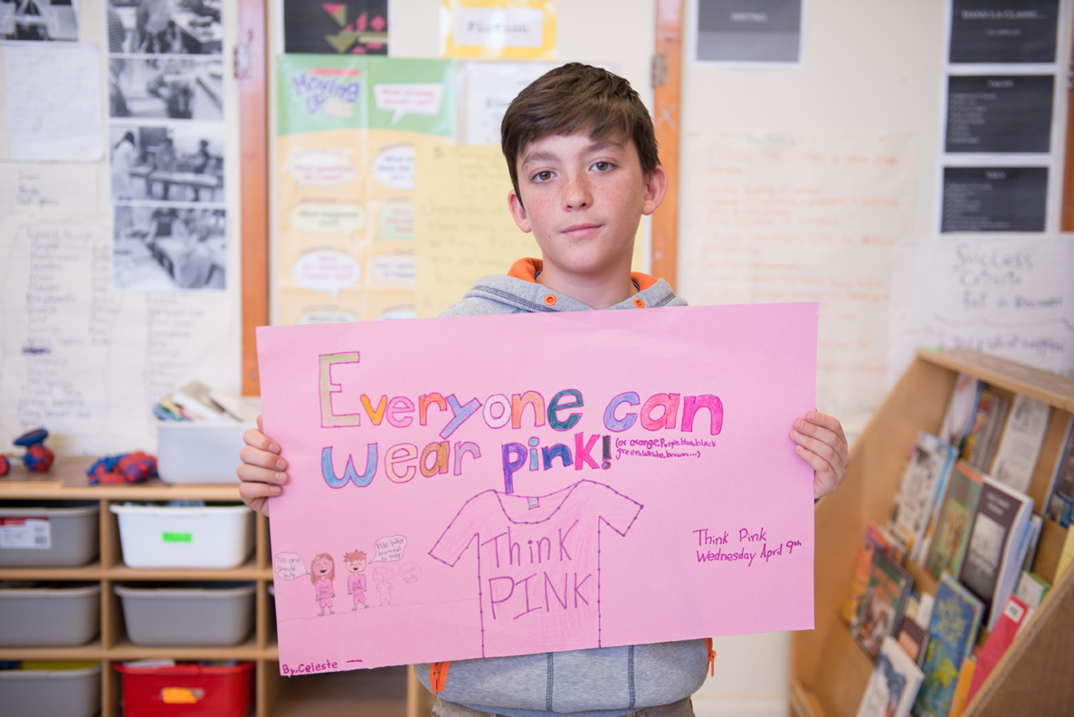 """Male student holding paper that says """"everyone can wear pink"""""""