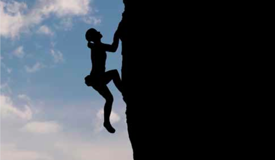 Silhouette of woman climbing cliff