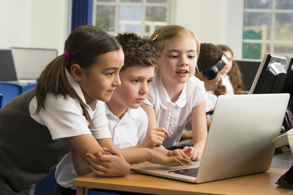 Young elementary students looking at laptop