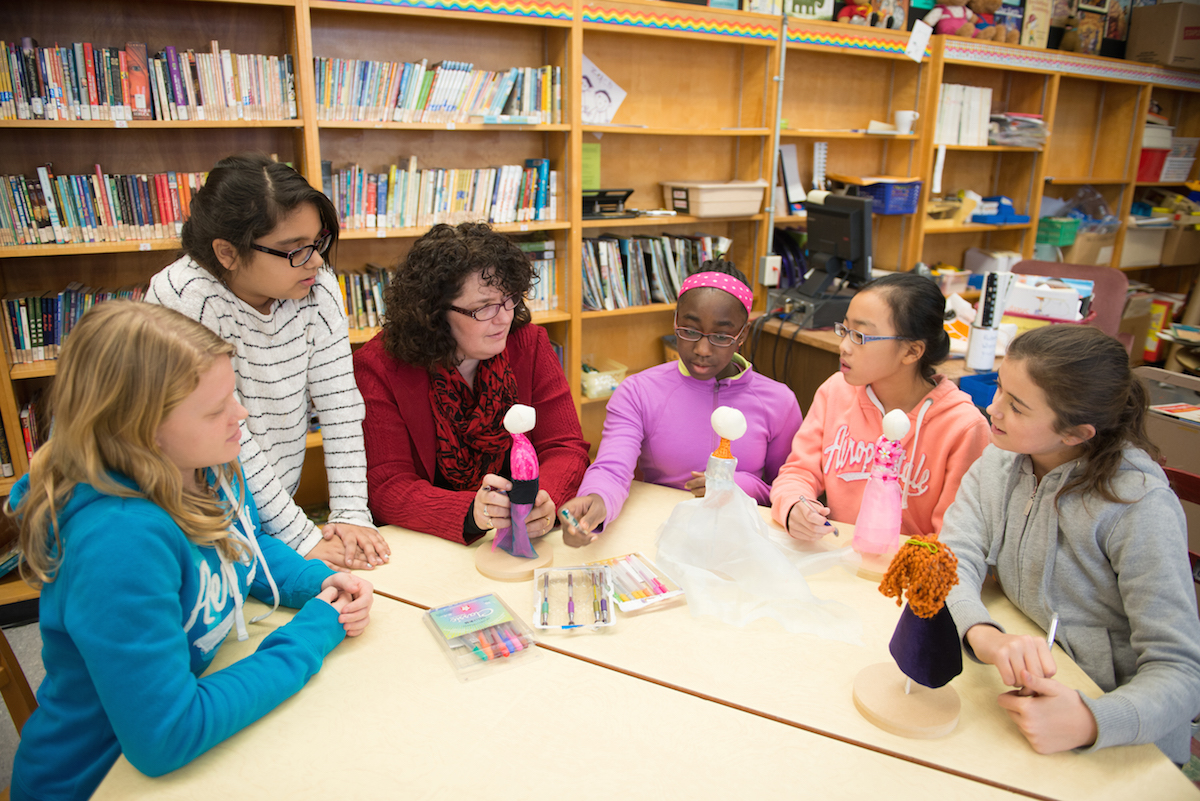 Elementary students and teacher sitting together working on dolls in library