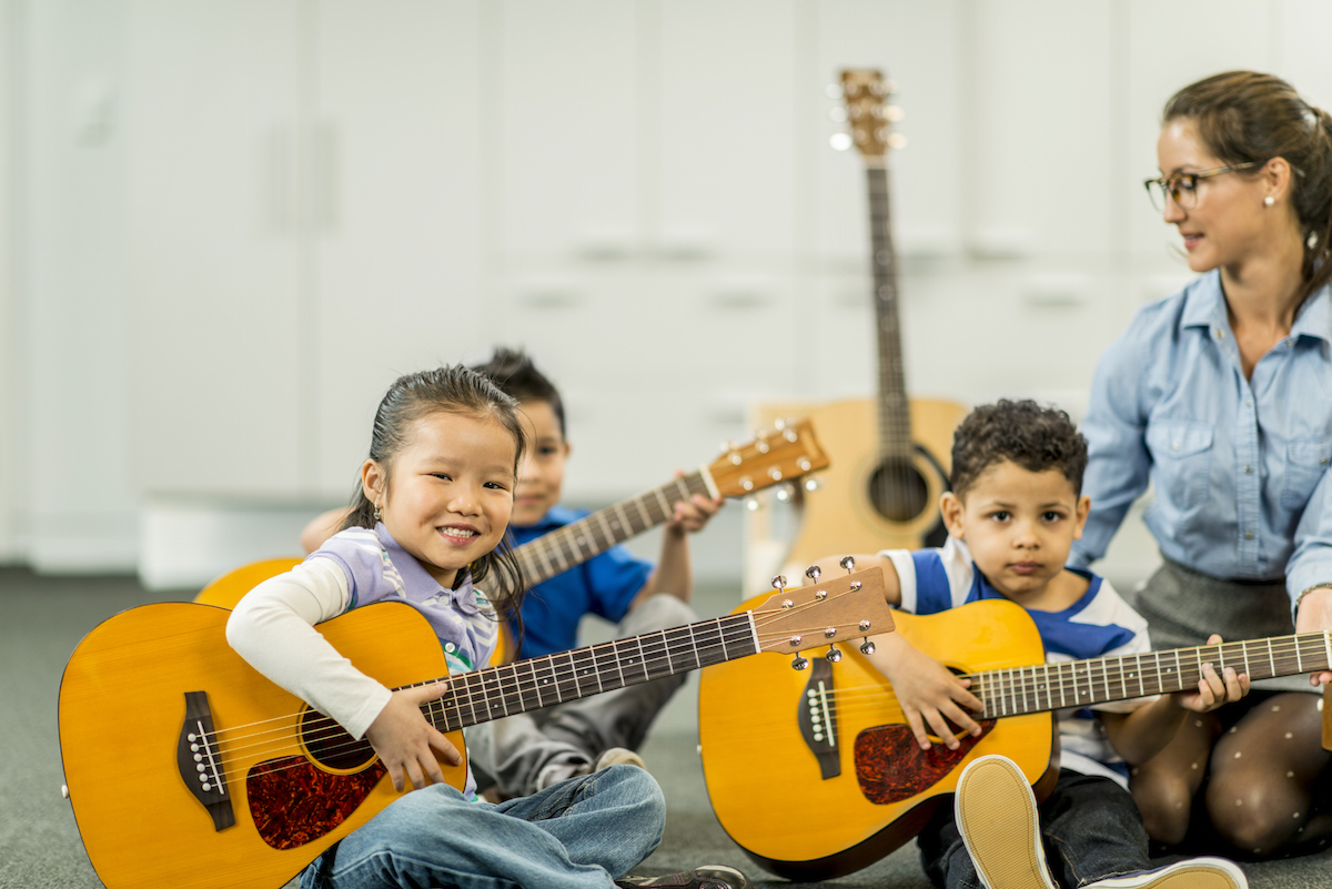Elementary students learning music with acoustic guitars