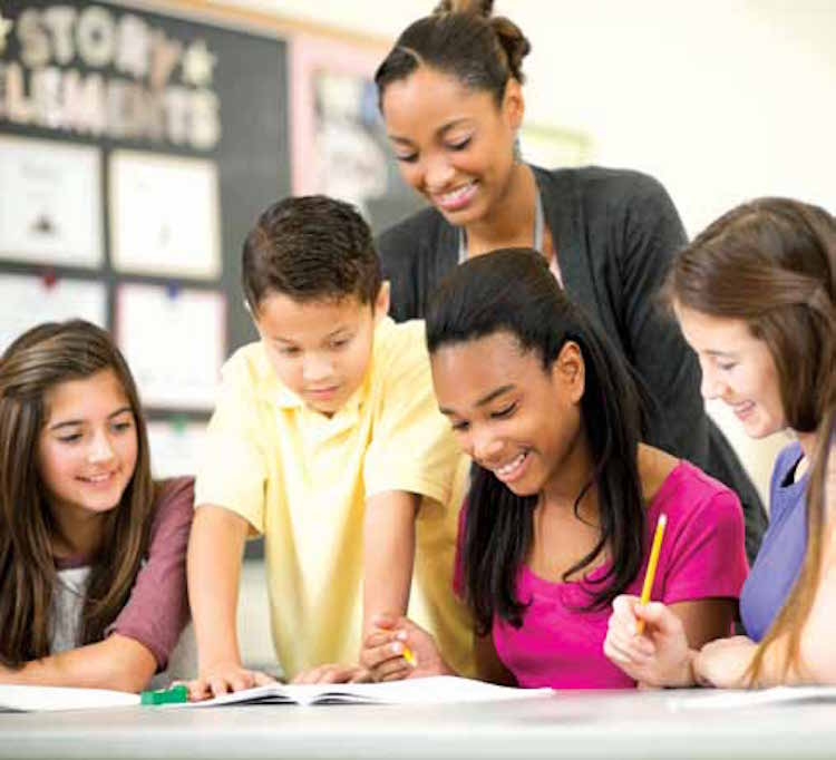 woman standing with children in classroom