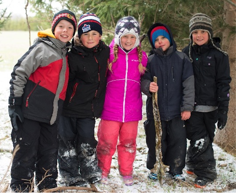 Children wearing snowsuits standing near wooded area