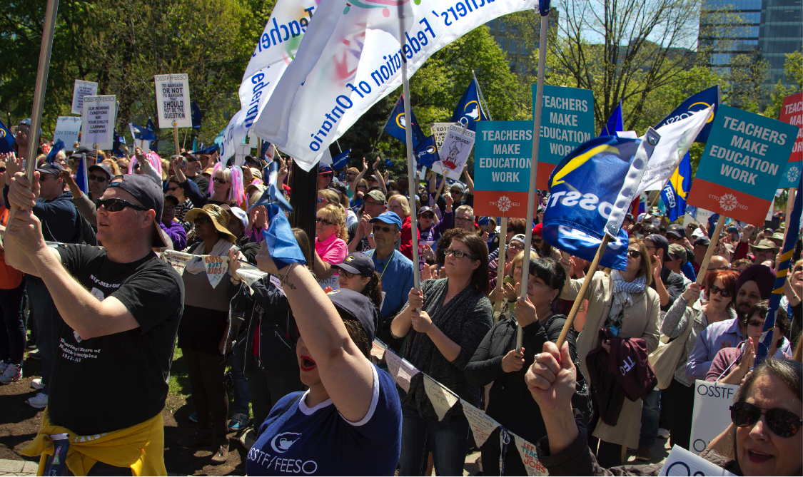 ETFO members standing with signs at rally