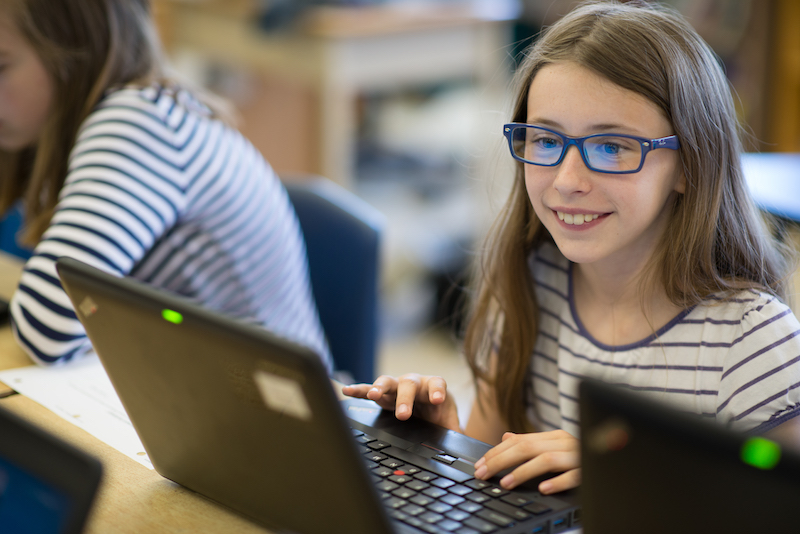 student using laptop and smiling